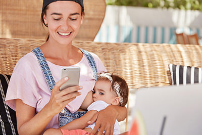 Young mother using smartphone while nursing infant